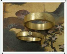 Trouwringen. Geelgouden ringen met hamerslag en diamant.