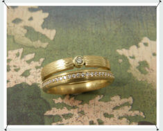 Geelgoud ring rondom diamant in pavé gezet