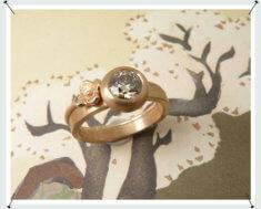 Ring, roodgouden structuur met 0,90 crt natuurlijk bruine briljant geslepen diamant. Met een vrolijke bloem aanschuifring ernaast.