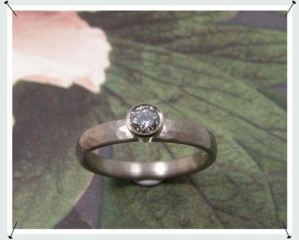 Verlovingsring, witgoud met fijne hamerslag en diamant.
