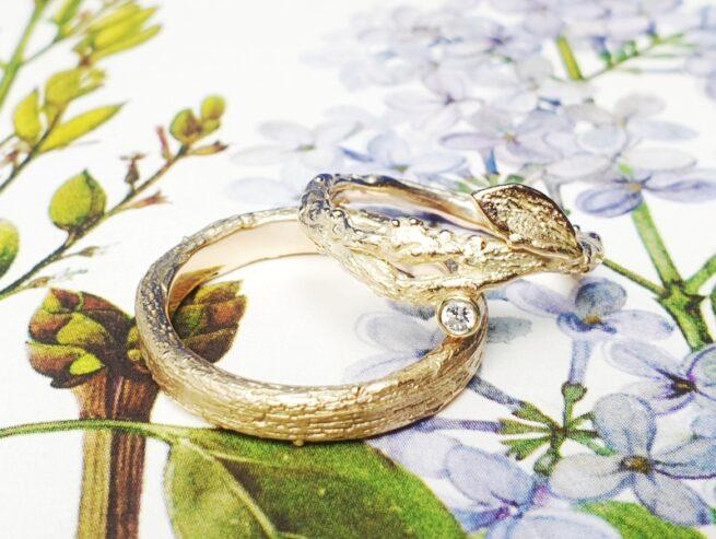 Geelgouden trouwringen 'Boomgaard'. Takjes met blaadje en diamant. Ontwerp en creatie van Oogst Goudsmeden.