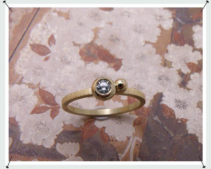 Deze geelgouden ring heeft een 0,10 crt ijsblauwe briljant geslepen diamant in een bolle zetting met een vrolijke bol. Speels en elegant!