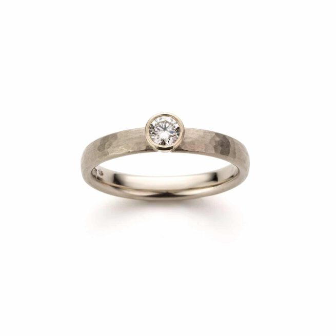 Witgouden verlovingsring met briljant geslepen diamant en hamerslag. Oogst goudsmeden.