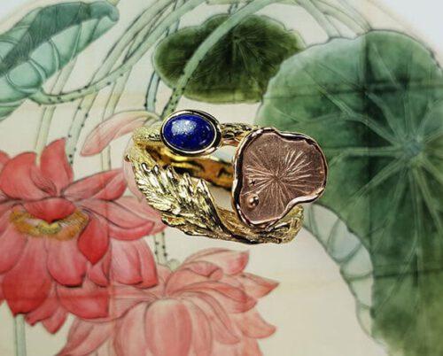 Ring 'Hortus' van eigen goud vervaardigde takje met een veertje, een roodgouden vijverblad en een lapis lazuli. Ontwerp vol symboliek. Oogst goudsmeden. Ring Botanical Garden created with heirloom gold and Lapis Lazuli. Design by Oogst
