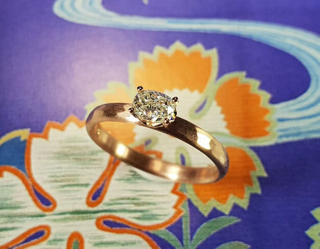 Verlovingsring 'Ritme'. Roodgouden ring met hamerslag en een ovaal geslepen diamant. Engagement ring 'Rhythm'. Rose golden ring with hammering and an oval cut diamond. Uit het Oogst atelier Amsterdam.
