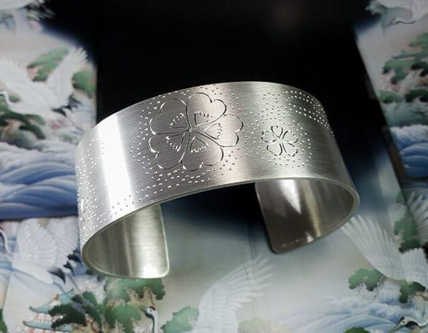 Zilveren klemarmband met handgravure van klavertjes bij de beek. Silver cuff with handengraved clovers. Oogst goudsmeden Amsterdam.