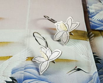 Witgouden Magnolia oorsieraden. White gold magnolia earrings with hand engraving and yellow gold details. Oogst goudsmid Amsterdam