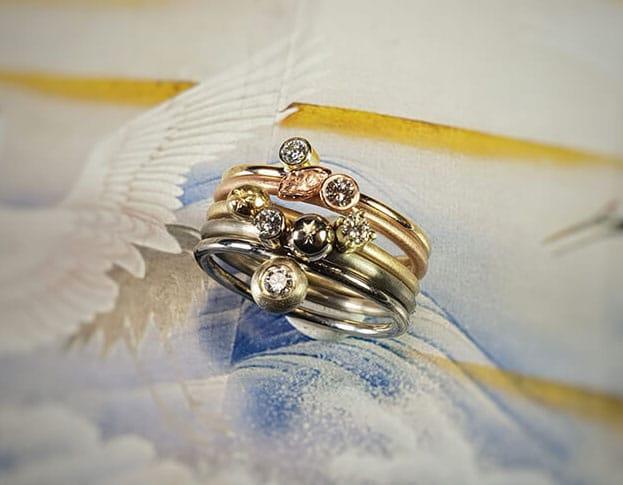 Verlovingsring 'Verzameling' geelgouden ring met eigen diamant, witgouden ring met van eigen goud vervaardigde 'sinaasappel' en eigen diamant, van eigen goud vervaardigde ring met sinaasappel en eigen diamant, roodgouden ring met blaadje en eigen diamant, witgouden ring met eigen diamant. Engagement ring 'Collection' yellow golden ring with heirloom diamond, white golden ring with 'orange' made of heirloom gold with heirloom diamond, ring made of heirloom gold with orange and heirloom diamond, rose golden ring with leaf and heirloom diamond, white golden ring with heirloom diamond. Oogst goudsmeden Amsterdam.