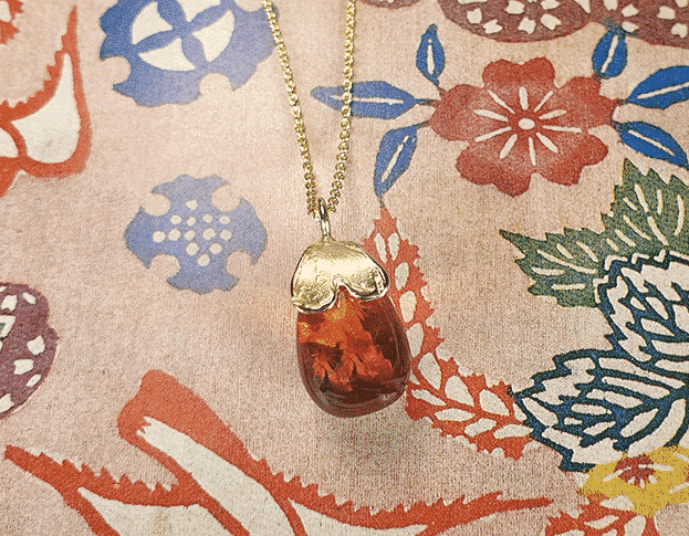 Yellow gold pendant with an amber drop and a heart shape. Push present with a gemstone inspired by the baby's name.  Oogst goldsmith Amsterdam