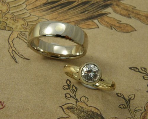 Trouwringen 'Boleet' en 'Eenvoud'. Ovale ring van eigen goud met eigen diamant uit een erfstuk. Witgouden ovale ring met een stip van eigen geelgoud. Wedding rings 'Boletus' & 'Simplicity'. Oval ring made from heirloom gold and diamond. White golden oval ring with yellow golden dot of heirloom gold. Uit het Oogst atelier Amsterdam.