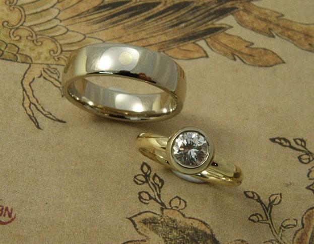 Trouwringen 'Boleet' en 'Eenvoud'. Ovale ring van eigen goud met eigen diamant uit een erfstuk. Witgouden ovale ring met een stip van eigen geelgoud. Wedding rings 'Boletus' & 'Simplicity'. Oval ring made from heirloom gold and diamond. White golden oval ring with yellow golden dot of heirloom gold. Uit het Oogst atelier Amsterdam.