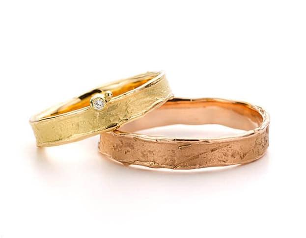 Roodgouden en geelouden trouwringen erosie. De geelgouden ring heeft een briljant geslepen diamant. Oogst goudsmeden Amsterdam.