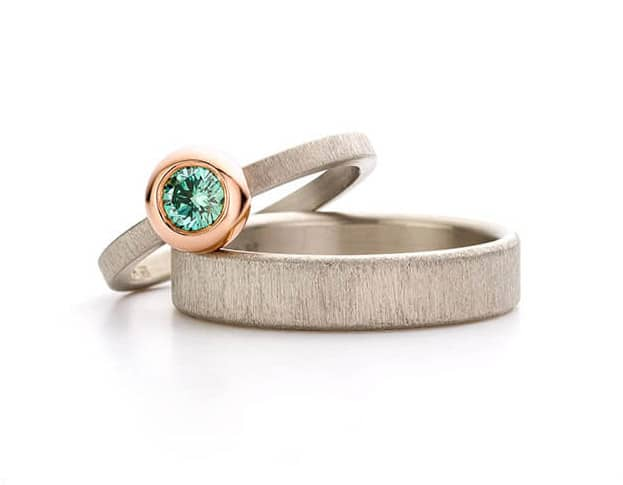 Witgouden trouwringen fluweel. Smalle ring met fancy Paraiba diamant in roodgouden boleet zetting. Oogst goudsmeden Amsterdam.
