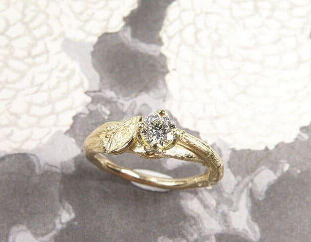 Verlovingsring 'Boomgaard'. Geelgouden ring overkruist takje met blaadje met 0,34 ct diamant. Engagement ring 'Orchard'. Yellow golden ring with twig, leaf and 0,34 crt diamond. Uit het Oogst atelier Amsterdam.