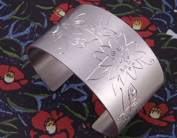 Zilveren armband met handgravure Passiebloem. Uit het Oogst goudsmid atelier. Silver cuff bracelet with hand engraving of a Passionflower. Made in the Oogst goldsmith studio.