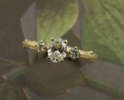Verlovingsring 'Boomgaard'. Geelgouden takje met een ovale 0,40 crt diamant en 2 0,05 crt diamanten. Engagement ring 'Orchard'. Yellow golden twig ring with oval 0,40 crt diamond and 2x 0,05 crt diamonds. Oogst goudsmeden Amsterdam.