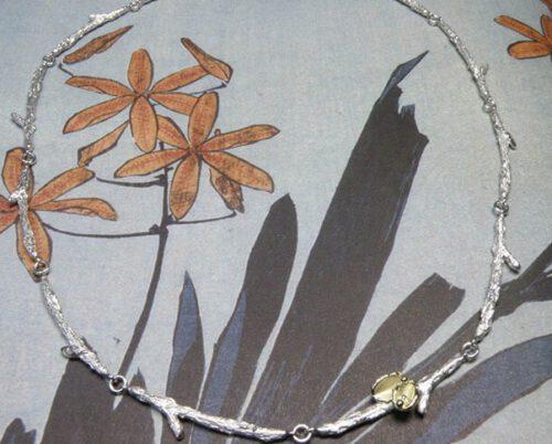 Zilveren takjes schakels met geelgouden blaadjes. Silver twigs necklace with yellow golden leafs. Oogst goudsmeden Amsterdam.