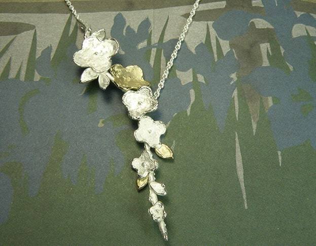 Collier 'In bloei' Bloemen en blaadjes op takjes van eigen geelgoud en zilver. Met een fijn anker collier gecombineerd. Uit het Oogst atelier Amsterdam. Necklace In Bloom, sweet flowers created from own silver and heirloom gold.