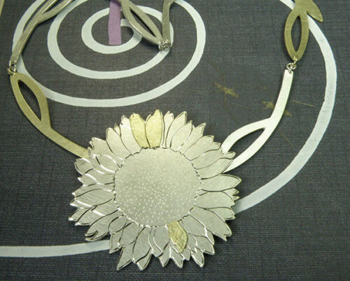 Zilveren Zonnebloem collier met geelgouden details en handgravure. Silver Sunflower necklace with yellow gold details and hand engravings. Uit het Oogst goudsmid atelier. Made in the Oogst goldsmith studio.