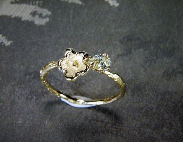 Verlovingsring 'In bloei'. Roségouden takje met een bloemetje en een 0,17 crt diamant. Engagement ring 'In bloom'. Rose golden twig with flower and a 0,17 crt diamond. Uit het Oogst atelier Amsterdam.