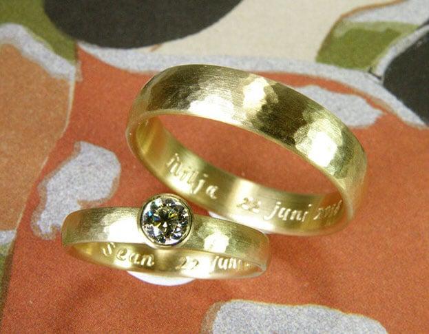 Geelgouden trouwringen gehamerd met diamant, bol van vorm.