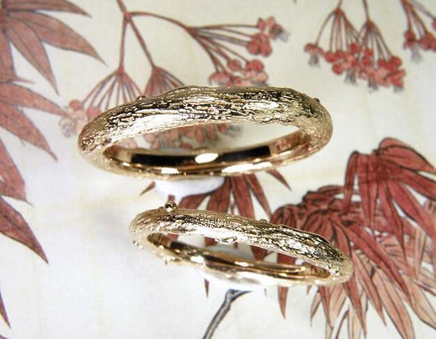 Takjes trouwringen van roodgoud, smalle ringen met organische structuur.