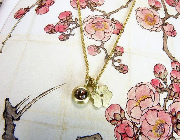 Geelgouden Japanse bloesem hanger en geelgouden hanger met bruine diamant. Necklace with a yellow golden Japanese blossom pendant and a yellow golden pendant with a brown diamond. Uit het Oogst atelier Amsterdam.
