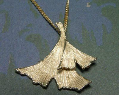 Hanger van eigen goud vervaardigde ginkgo blaadjes. Maatwerk uit het Oogst atelier Amsterdam. Ginkgo leaf pendant, made from heirloom gold.