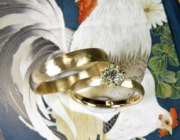 Roségouden trouwringen met hamerslag. Met briljant geslepen diamant cape in een geelgouden tulp zetting. Chaton zetting. Modern solitaire. Hammered wedding rings. Pink gold wedding rings. Rose gold wedding rings. Oogst goudsmid Amsterdam.