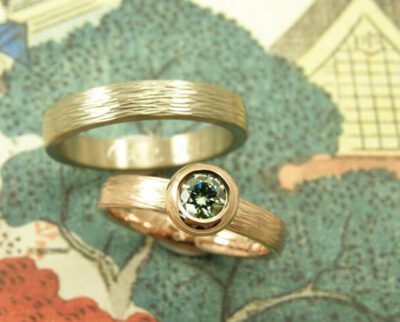 Trouwringen 'Boleet' en 'Ritme'. Roodgouden ring met hamerslag en paraiba green diamant. Witgouden ring met hamerslag. Wedding rings 'Boletus' & 'Rhythm'. Rose golden ring with hammering and paraiba green diamond. White golden ring with hammering. Oogst goudsmeden Amsterdam.
