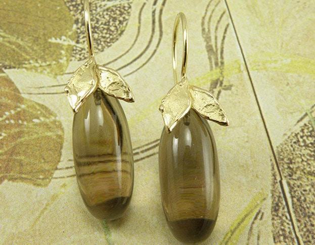 Geelgouden blaadjes met rookkwarts pampels en een krul. Yellow golden earrings with smokey quartz. Oogst goudsmeden Amsterdam.
