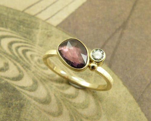 Verlovingsring Ton sur ton geelgouden ring met paarse saffier en diamant. Engagement ring Ton sur ton yellow golden ring with purple sapphire and diamond. Oogst goudsmeden Amsterdam.