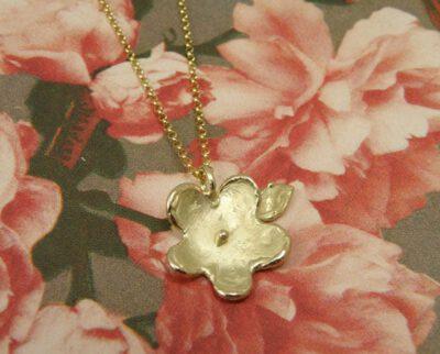 Geelgouden bloemetjeshanger aan fijn ankercollier. Yellow golden flower pendant on fine necklace. Uit het Oogst atelier Amsterdam.