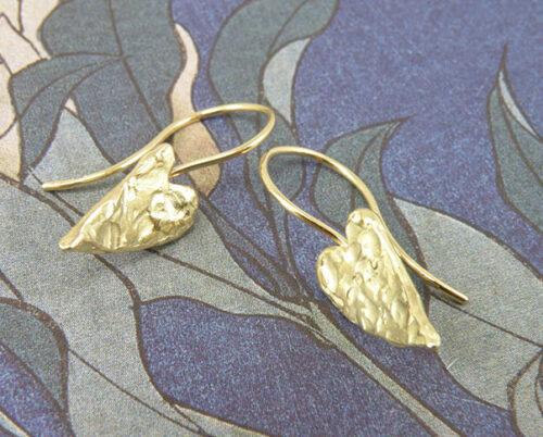 Geelgouden hartjes oorsieraden met stoere structuur en krul. Yellow golden heart earrings with structure. Oogst goudsmeden Amsterdam.