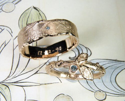 Trouwringen 'Erosie' & 'Boomgaard'. Roodgouden ring met een takje, 2 blaadjes en een ijsblauwe diamant. Roodgouden structuur ring met ijsblauwe diamant. Wedding rings 'Erosion' & 'Orchard'. Rose golden ring with a twig, 2 leafs and an ice blue diamond. Rose golden ring with structure and an ice blue diamond. Oogst goudsmeden Amsterdam.
