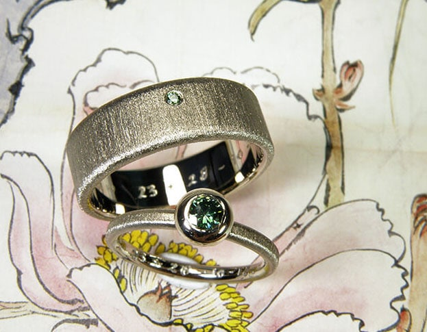 Wedding rings Simplicity white gold ring with a green diamond and white gold textured ring with a Velvet finish. Goldsmith Amsterdam. Oogst wedding bands.