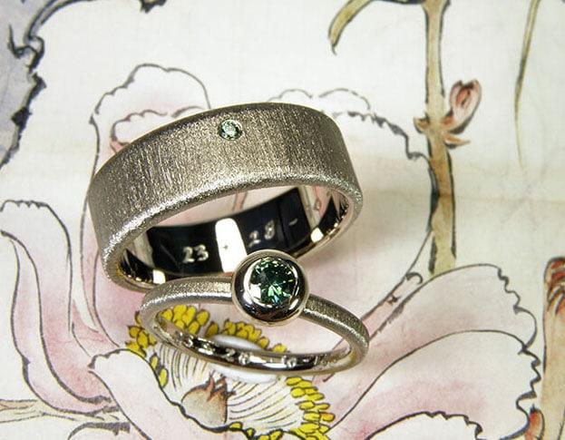 Witgouden strakke trouwringen met fancy groene diamant en fluweel matte afwerking.