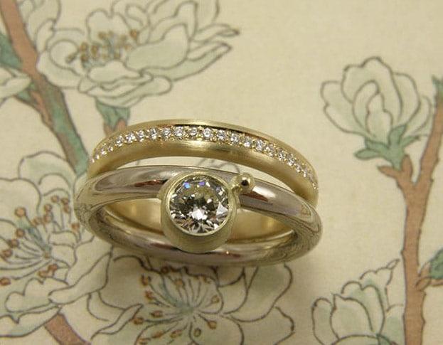 Aanschuifringen 'Eenvoud'. Geelgouden ring met diamanten rondom. Witgouden ring met een briljant geslepen diamant en een besje. Moderne klassieke trouwringen. Uit het Oogst atelier Amsterdam.