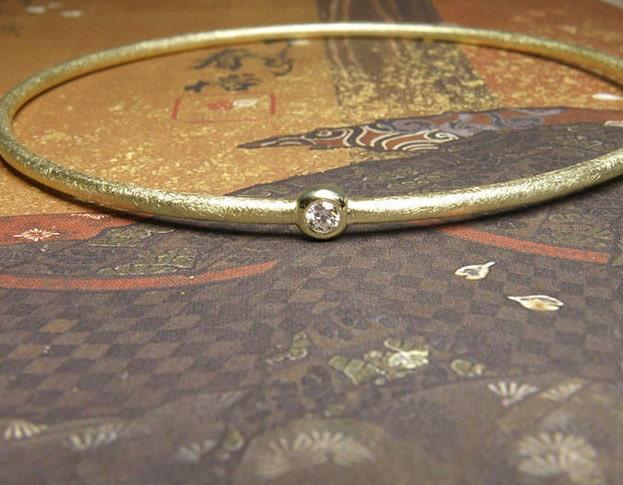 Armband 'Eenvoud' geelgouden rinkelband met eigen diamant. Bracelet 'Simplicity' yellow golden bangle with heirloom diamond. Uit het Oogst atelier Amsterdam.