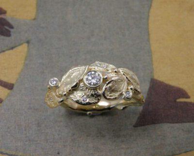 Ring 'Boomgaard' blaadjes ring uit oud goud vervaardigd met 0,17 crt, 0,02 crt, 0,01 crt en 6 x 0,005 crt diamant. Ring 'Orchard' leaf ring made from heirloom gold with 0,17 crt, 0,02 crt, 0,01 crt and 6x 0,005 crt diamonds. Oogst goudsmeden Amsterdam.