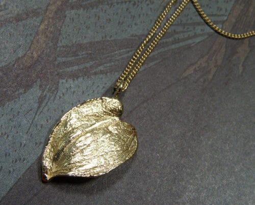 'Boomgaard' collier met geelgouden hartvormig blad bungelend aan eenverfijnd gourmet schakelcollier. 'Orchard' necklace with yellow golden hart shaped leaf. Oogst Amsterdam.