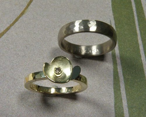 Trouwringen 'Ritme'. Geelgouden ring met kussen hamerslag en bloem met witgouden blaadje en bruine diamant. Witgouden ring met kussen hamerslag. Wedding rings 'Rhythm'. Yellow golden ring with hamering and flower with white golden petals and brown diamond. Yellow golden ring with hammering. Oogst goudsmeden Amsterdam.