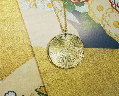 Hanger 'Cirkel' van eigen goud vervaardigde hanger met een verfijnde streepjesstructuur aan een schakel collier. Pendant 'Circle' pendant made of heirloom gold with delicate stripe structure on chain necklace. Uit het Oogst atelier Amsterdam.
