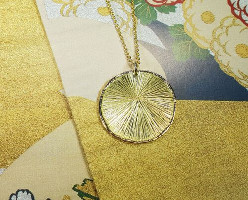 Hanger 'Cirkel' van eigen goud vervaardigde hanger met een verfijnde streepjesstructuur aan een schakel collier. Pendant 'Circle' pendant made of heirloom gold with delicate stripe structure on chain necklace. Uit het Oogst atelier Amsterdam.