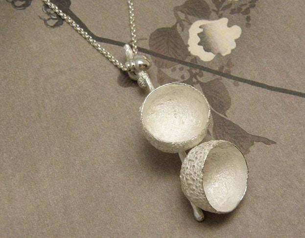Zilveren hanger Eikendopjes met kevertje. Silver pendant Acorns with a ladybug. Uit het Oogst goudsmid atelier. Made in the Oogst goldsmith studio.