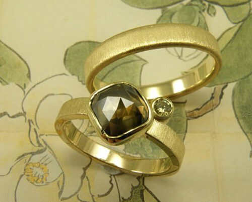 Trouwringen 'fluweel'. Geelgouden ring met een diamant en een olijf diamant. Geelgouden ring met streepjes afwerking. Wedding rings 'Velvet'. Yellow golden ring with a diamond and an olive green diamond. Yellow golden ring with stripey finish. Oogst goudsmeden Amsterdam.