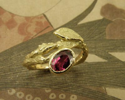 Verlovingsring 'Boomgaard'. Geelgouden takje met blaadje en een ovale robijn. Engagement ring 'Orchard'. Yellow golden twig with leaf and oval ruby. Uit het Oogst atelier Amsterdam.
