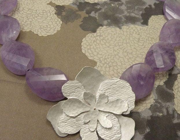 Zilveren hortensia met stofstructuren en amethist. Silver hydrangea necklace with fabric structure and amethyst. Oogst goudsmeden Amsterdam.