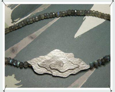 Labradoriet collier met zilveren sluiting van Batik motief. Necklace with labradorite and a silver Batik motive. Oogst goudsmid Amsterdam