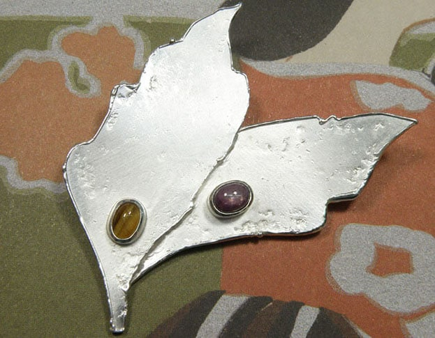 Zilveren broche Bladeren met tijgeroog en ster robijn. Uit het Oogst atelier. Silver brooch Leafs, with tiger eye and star ruby. Made in the Oogst goldsmith studio.